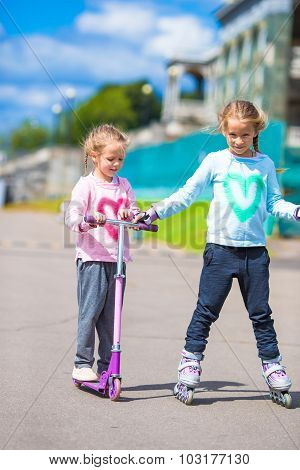 Two little girls roller skating and riding a scooter in the park outdoor