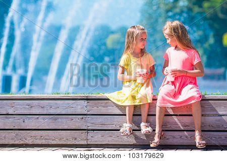 Little happy girls have fun near street fountain at hot sunny day