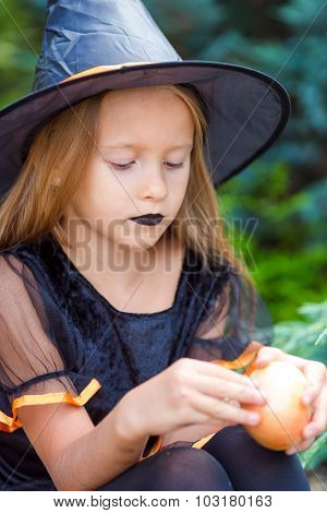 Portrait of cute little girl wearing witch costume with broom on Halloween