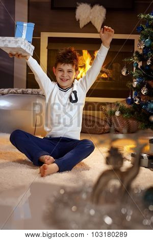 Happy little boy lifting up high christmas present, smiling.