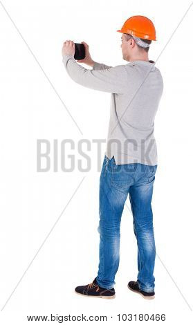 Backview of an engineer in construction helmet stands and enjoys tablet or using a mobile phone. Standing young guy. Rear view people collection.  backside view of person.