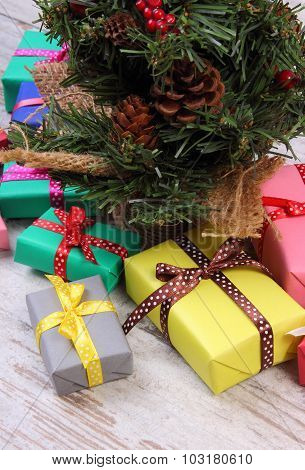 Wrapped Colorful Gifts For Christmas With Christmas Tree On Old White Plank