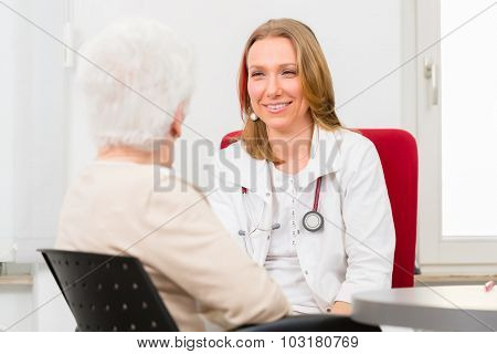 Young female doctor sitting with pensioner in surgery consultation hour at desk