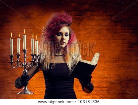 Beautiful witch casting a spell using a magical book and a candlestick. Halloween concept.