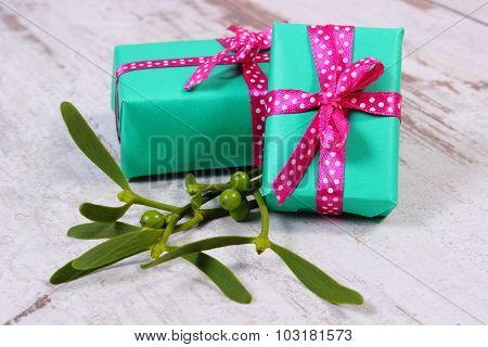 Wrapped Green Gifts For Christmas And Mistletoe On Old Wooden Background