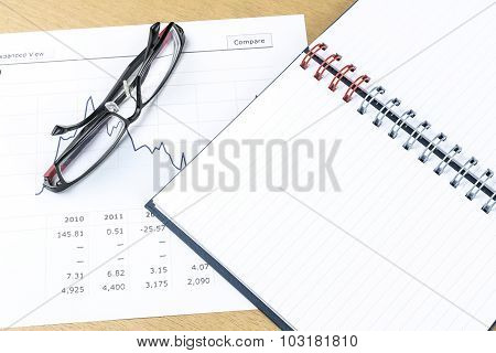 Workplace With Pen, Notebook, Glasses And Financial Report