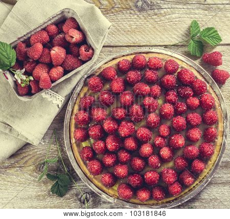 Tart with raspberries on a wooden table. top view