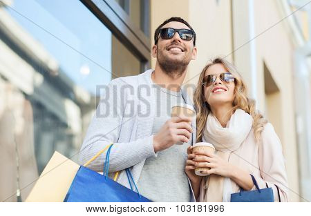 sale, consumerism and people concept - happy couple with shopping bags and coffee paper cups at shop window on city street