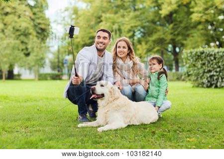family, pet, animal, technology and people concept - happy family with labrador retriever dog taking picture by smartphone on selfie stick in park