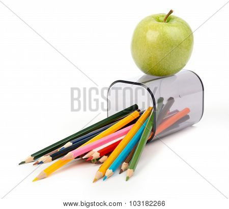 Fallen pencil cup with crayons and apple