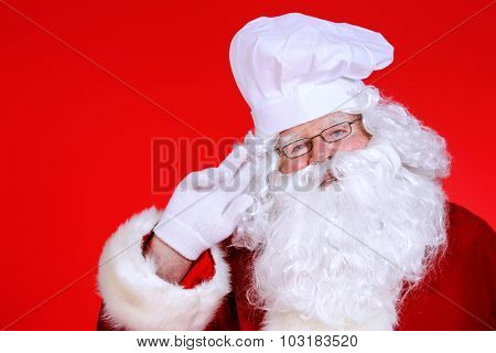 Jolly Santa Claus in a chef's hat over festive red background. Copy space. Christmas treats.