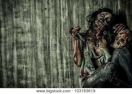 Frightening bloody zombie girl with a skull. Halloween.