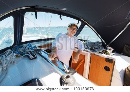 sailing, age, tourism, travel and people concept - happy senior man in captain hat on sail boat or yacht floating in sea