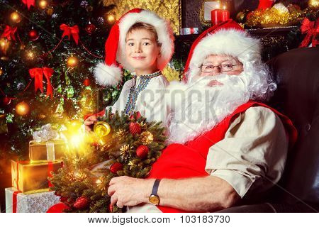 Santa Claus in his everyday clothes in Christmas home décor. Happy little boy helps Santa Claus get ready for Christmas.