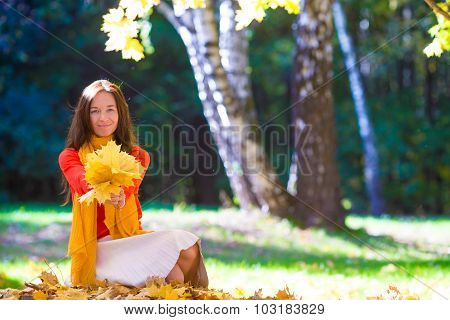 Happy young woman with yellow maple leaves outdoors at beautiful autumn park