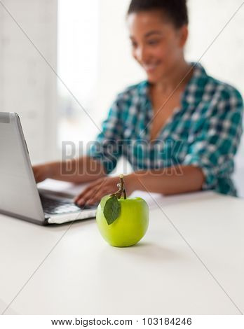 education, people, friendship, technology and learning concept - close up of happy high school african student girl with laptop computer and green apple in classroom