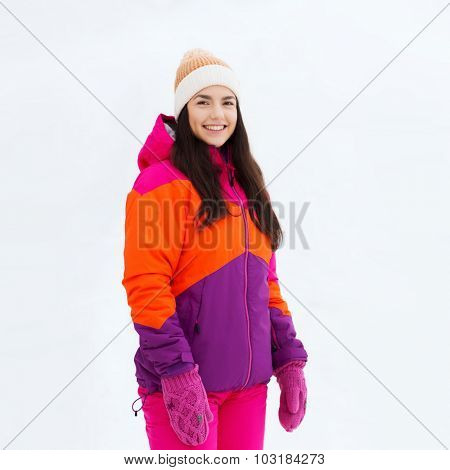 winter, leisure, clothing and people concept - happy young woman or teenage girl in winter clothes outdoors
