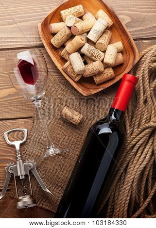 Red wine bottle, wine glass, bowl with corks and corkscrew. View from above over rustic wooden table background