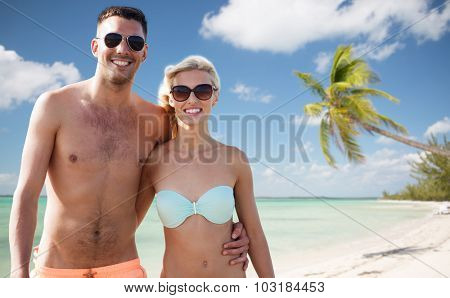 love, travel, tourism, summer and people concept - smiling couple on vacation in swimwear and sunglasses hugging over tropical beach background