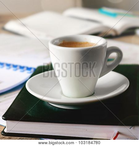 Cup Of Coffee Stands On A Diary