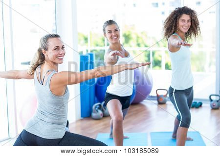 Portrait of women doing warrior II pose in fitness studio