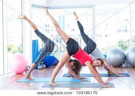 Women doing half downward dog pose in fitness studio