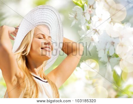 fashion, people and summer holidays concept - beautiful woman in hat and dress sunbathing over green blooming garden background