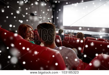 cinema, entertainment and people concept - happy friends or couple watching movie in theater on last row and talking from back over snowflakes