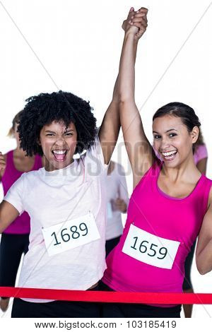 Portrait of cheerful winner athletes crossing finish line with arms raised against white background