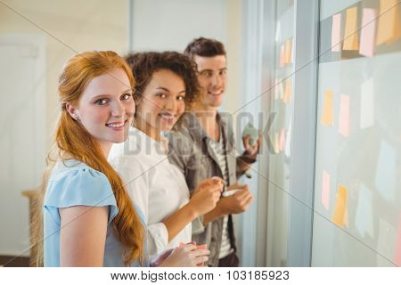 Portrait of smiling business people standing by glass wall during meeting in office