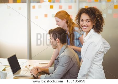 Portrait of businesswoman with colleagues using laptop at work in office