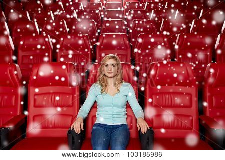 cinema, entertainment and people concept - young woman watching movie alone in empty theater auditorium with snowflakes