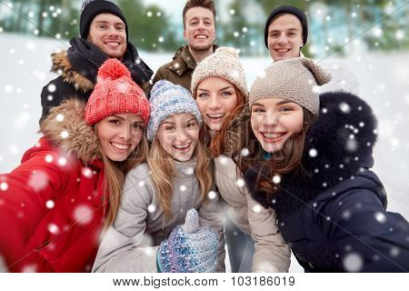 winter, technology, friendship and people concept - group of smiling men and women taking selfie and showing thumbs up outdoors