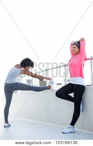 Full length of women exercising by railing