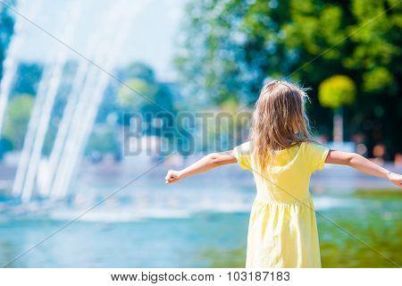 Little happy girl have fun near street fountain at hot sunny day