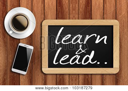 Coffee, Phone And Chalkboard With Learn And Lead Words