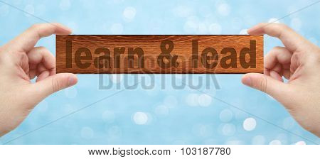 Hands Holding A Wood Engrave With Word Learn And Lead