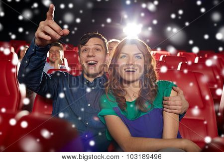 cinema, entertainment, gesture, emotions and people concept - happy couple watching movie pointing finger to screen in theater with snowflakes