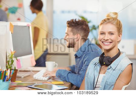 Portrait of smiling businesswoman sitting against employees working in creative office
