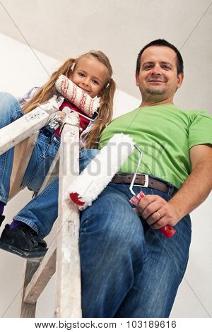 Happy room painters on a ladder - father and little girl smiling