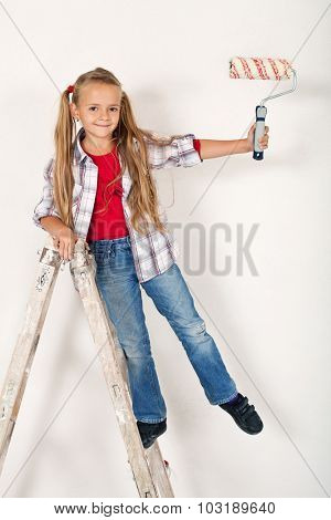 Happy little girl on a ladder with roller brush - having fun repainting the room