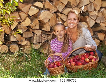 Happy harvesters in autumn - laughing child and woman with red apples in baskets