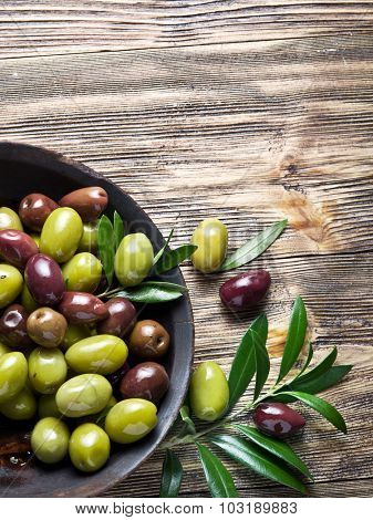 Wooden bowl full of olives and olive twigs besides it.