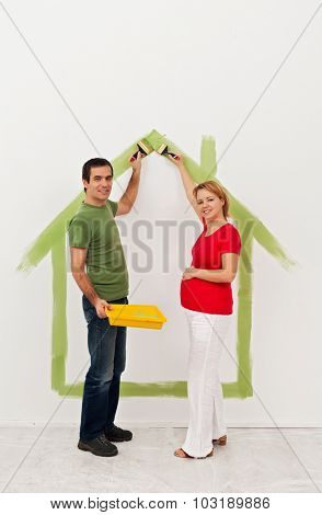 Young couple expecting a baby - preparing the child room in their new home