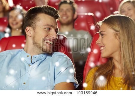 cinema, entertainment and people concept - happy friends or couple watching movie and talking in theater with snowflakes