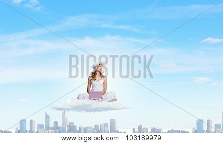Young lady sitting on cloud and using laptop