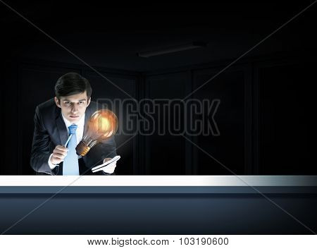Young businessman examining glass glowing light bulb