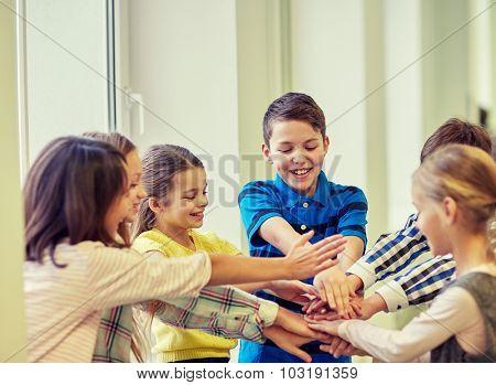 education, elementary school, children, break and people concept - group of smiling school kids putting hands on top in corridor
