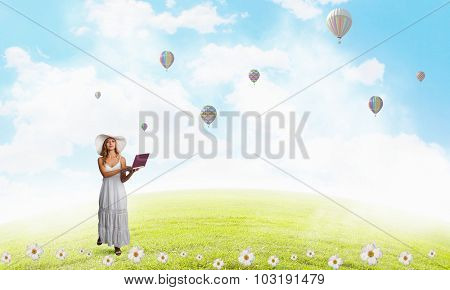 Young lady outdoor with laptop in hands