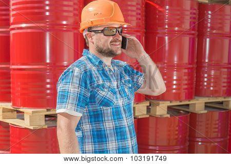 Worker in safety helmet standig in front of metal barrels